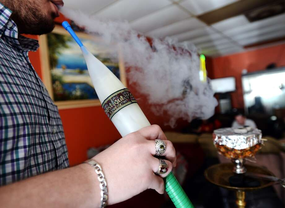 Haytham Abdel smokes a specially prepared hookah at the Jerusalem Hookah Cafe on Tuesday. The special arrangement involves a halved pineapple and a larger ice-cooled hose. The Jerusalem Hookah Cafe has been serving up Middle Eastern cuisine as well as hookahs to the Beaumont area since 2009. Photo taken Tuesday, 3/18/14 Jake Daniels/@JakeD_in_SETX
