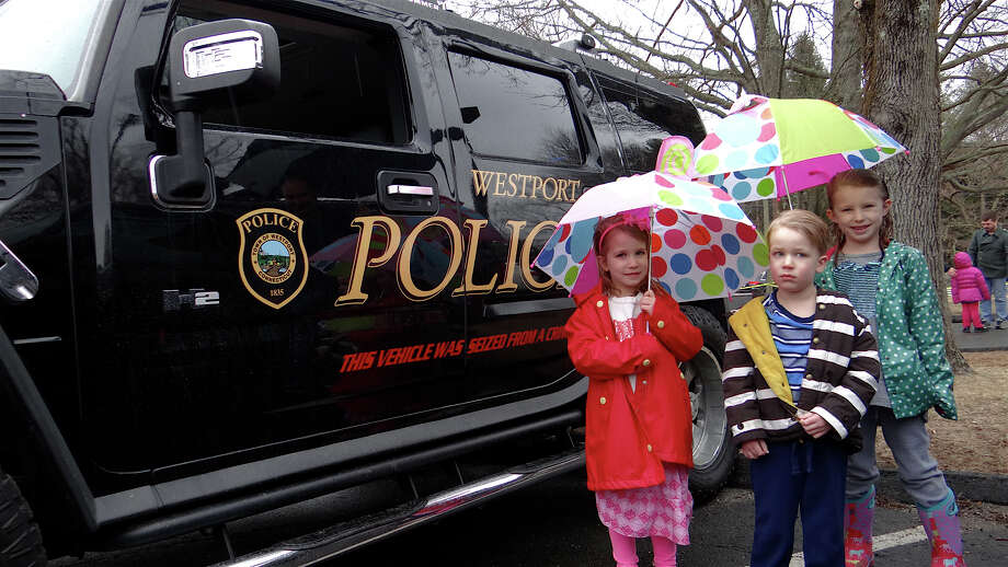 Avery, William and Madeleine Speller, ages 5, 4 and 6, of Westport, beside a Westport Police Humvee at the annual Touch-A-Truck event Saturday. Photo: Mike Lauterborn / Westport News