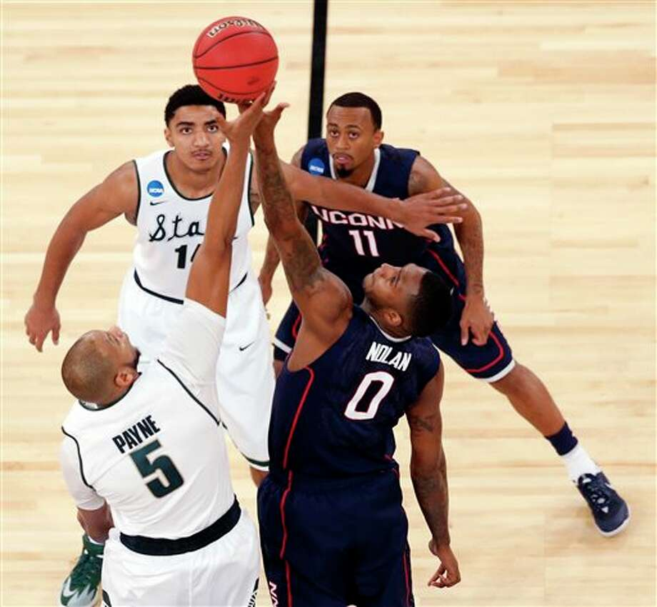 Michigan State forward  Adreian Payne (5) and Connecticut forward Phillip Nolan (0) go up for  the tip-off as Michigan State's Gary Harris, top left, and Connecticut's  Keith Appling (11) look on during the first half in a regional  semifinal at the NCAA college basketball tournament on Sunday, March 30,  2014, in New York. (AP Photo/Julio Cortez)