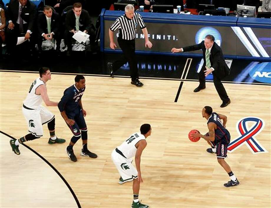 Michigan State head coach Tom  Izzo, top right, talks to his team during the first half in a regional  semifinal at the NCAA college basketball tournament against Connecticut,  Sunday, March 30, 2014, in New York. (AP Photo/Julio Cortez)