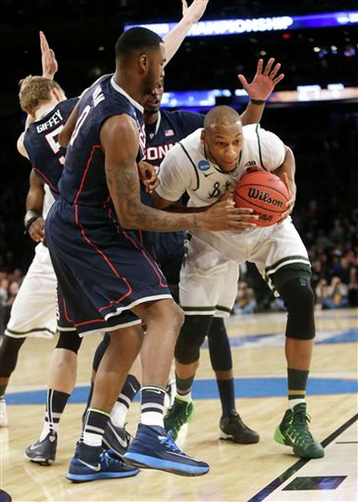 Michigan State's Adreian Payne, right, tries to move the ball past Connecticut's Phillip Nolan in the first half of a regional final at the NCAA college basketball tournament on Sunday, March 30, 2014, in New York. (AP Photo/Frank Franklin II)