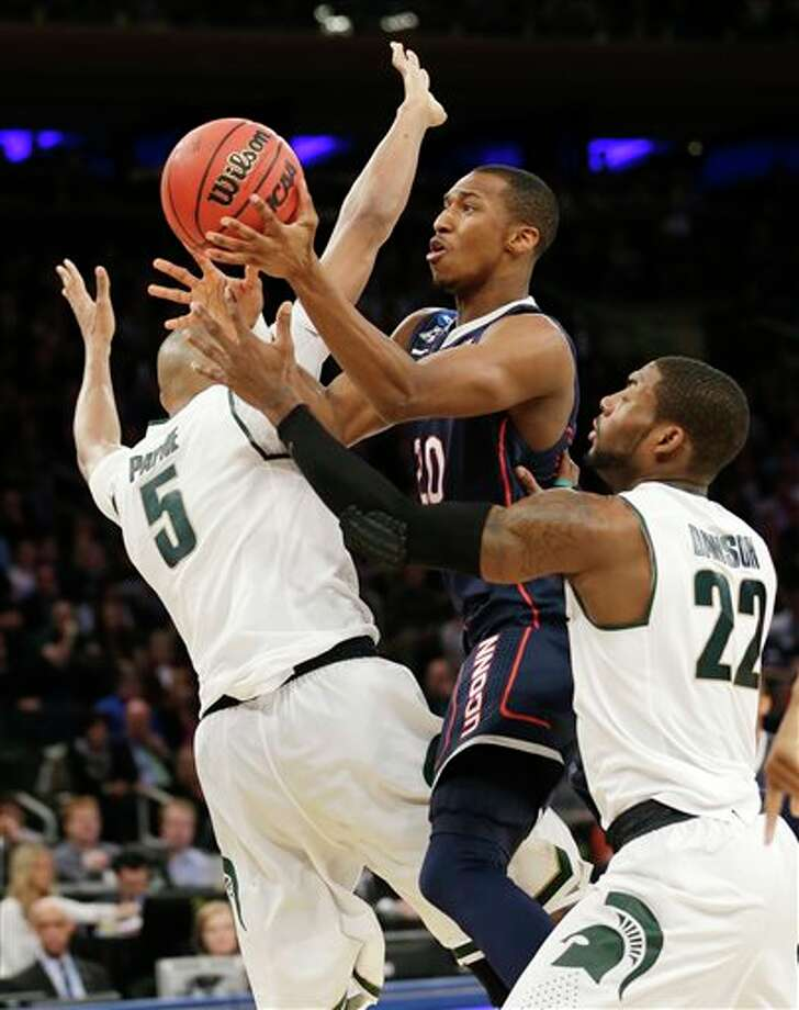 Connecticut's Lasan Kromah,  center, goes up between Michigan State's Adreian Payne, left, and  Branden Dawson in the first half of a regional final at the NCAA college  basketball tournament on Sunday, March 30, 2014, in New York. (AP  Photo/Seth Wenig)