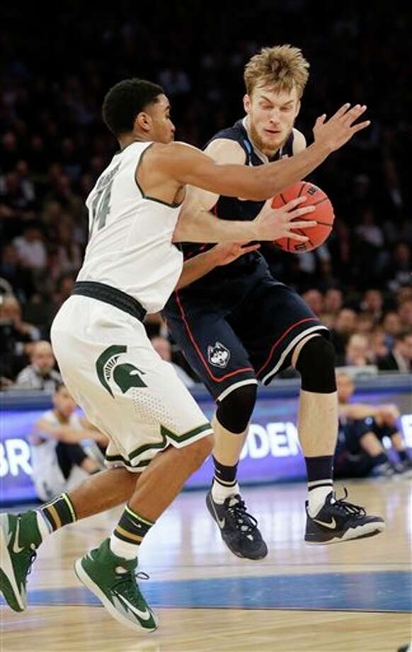 Connecticut's Niels Giffey,  right, drives past Michigan State's Gary Harris in the first half of a  regional final at the NCAA college basketball tournament on Sunday,  March 30, 2014, in New York. (AP Photo/Seth Wenig)