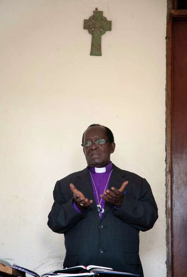 In this photo taken Sunday, March 16, 2014, Rev. Christopher Senyonjo, 82, gives a sermon on human sexuality at his makeshift church, the size of a small office, in Kampala, Uganda. Dressed in a purple shirt and white collar that highlight his Anglican faith, Bishop Senyonjo doesn�t organize his Sunday evening prayers for homosexuals only, but his sermons attract many gays who are familiar with his sympathetic views in a country where other Christian preachers have led Uganda's anti-gay crusade. Photo: AP / AP