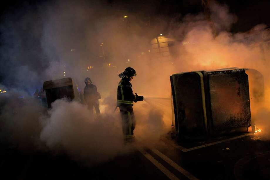 Firefighters extinguish burning trash containers following clashes between protesters and police officers during a demonstration against a reform of the penal code and an upcoming trial of protesters detained during a demonstration in the Parliament of Catalonia in 2011, in Barcelona, Spain, Saturday, March 29, 2014. Photo: Emilio Morenatti, AP / AP