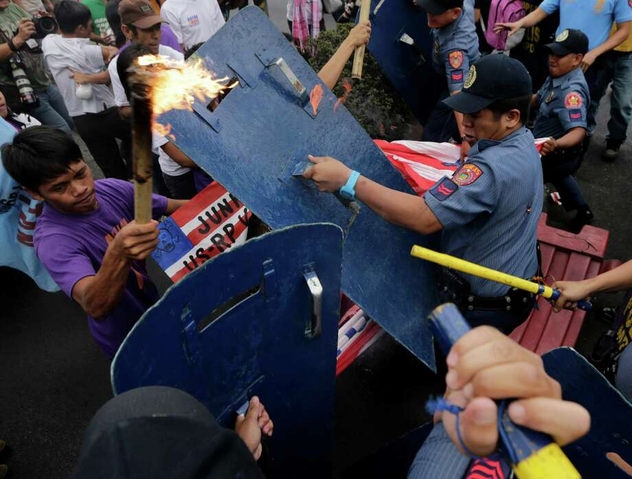 "Protesters clash with riot police during a protest against the ongoing talks between the Philippines and the United States on the Enhanced Defense Cooperation near U.S. Embassy in Manila, Philippines, Thursday, March 27, 2014. The protesters, who are also opposed to the forthcoming visit of U.S. President Barack Obama, that the possible agreement will pave the way for the long-term presence of U.S. troops in the country and the ""unlimited and unqualified use of Philippine bases and facilities by U.S. forces."" Photo: Uncredited, AP / AP2014"