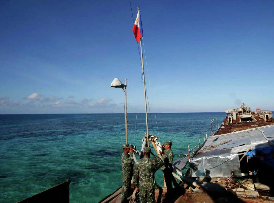 Philippine Marines raise the Philippine flag on the first day of their deployment on the dilapidated navy ship LT57 BRP Sierra Madre at the disputed Second Thomas Shoal, locally known as Ayungin Shoal,  Sunday, March 30, 2014 off the South China Sea. On Saturday, China Coast Guard attempted to block the Philippine government vessel AM700 carrying fresh troops and supplies, but the latter successfully managed to dock beside the ship to replace troops who were deployed for five months. Photo: Bullit Marquez, AP / AP