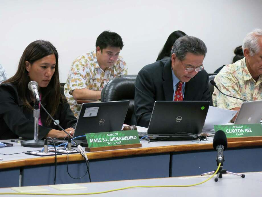 Hawaii State Sen. Clayton Hee, right, reads proposed changes to a prostitution bill during a committee hearing on Friday, March 28, 2014, at the Hawaii state Capitol in Honolulu. The bill, as amended, would end a provision in state law that allows police during investigations to have sex with prostitutes. Photo: Sam Eifling, AP / AP