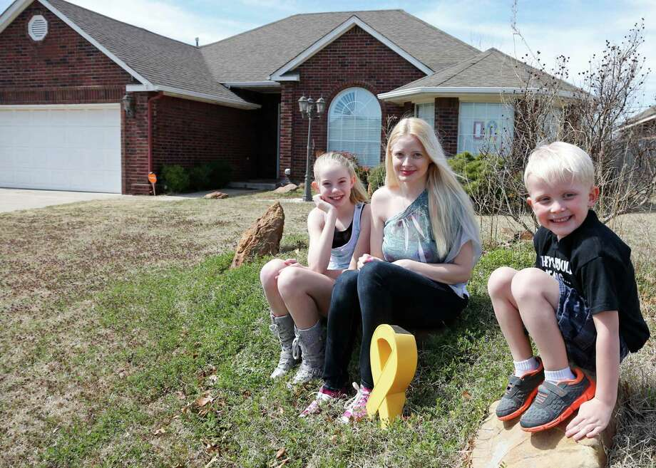 In this Monday, March 17, 2014 photo, Jennifer Hunt, center, poses for a photo outside her home with her son Trystan Morgan, 7, and daughter Silver Templeton, 11, in Noble, Okla. Hunt, whose husband was a soldier killed in the Fort Hood shooting, could get relief from a $6,000 tax bill under a measure Oklahoma legislators are considering that would grant some families benefits similar to those given after acts of terrorism. Photo: Sue Ogrocki, AP / AP