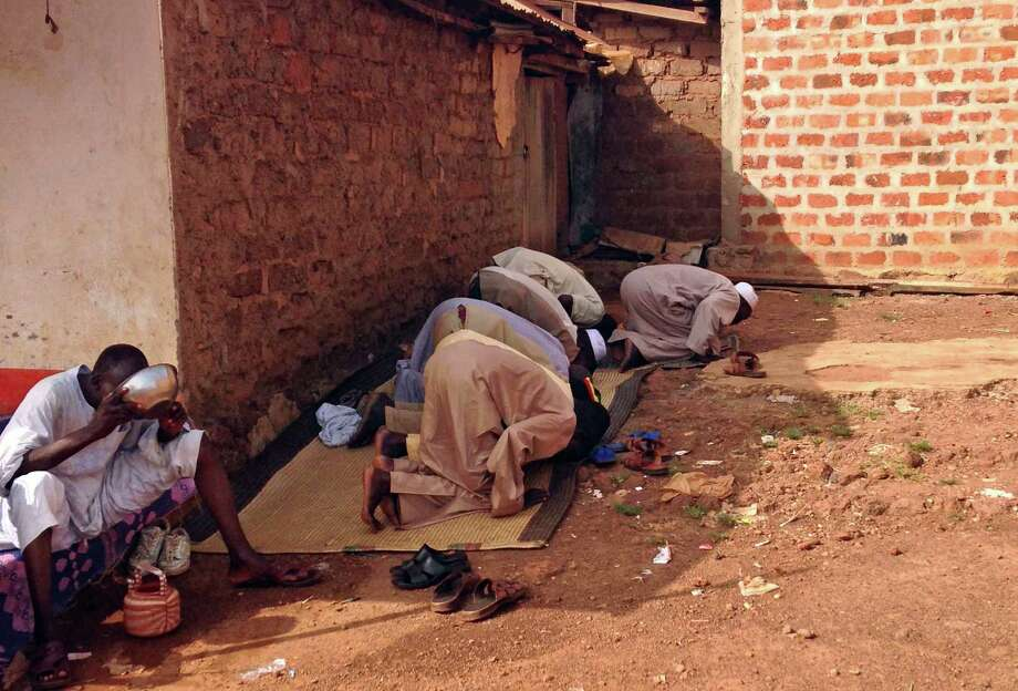In this photo taken on Wednesday, March 5, 2014, Muslims pray outside a building in the  besieged town of Boda, Central African Republic. There is only one neighborhood in Boda where Muslims are safe from the bullets and machetes of Christian militia fighters. Those who venture out have been killed, their throats slit or their cars showered in gunfire. The town is home to one of the largest Muslim communities left in Central African Republic, though their plight is mirrored throughout the country. The about 4,000 Muslims who remain here are suffering in isolation and say they just want to leave for good after months of being targeted by the militiamen. Photo: Krista Larson, AP / AP