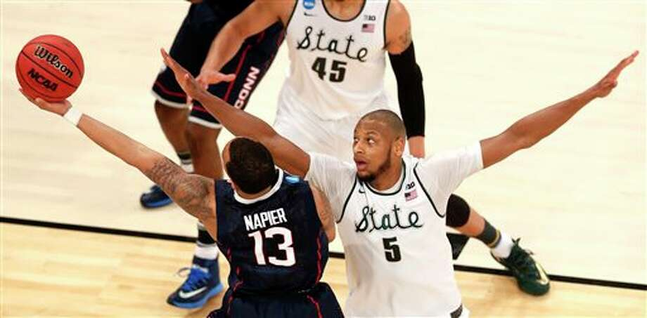 Connecticut guard Shabazz  Napier (13) goes up for a shot against Michigan State forward Adreian  Payne (5) during the first half in a regional semifinal at the NCAA  college basketball tournament, Sunday, March 30, 2014, in New York. (AP  Photo/Julio Cortez)