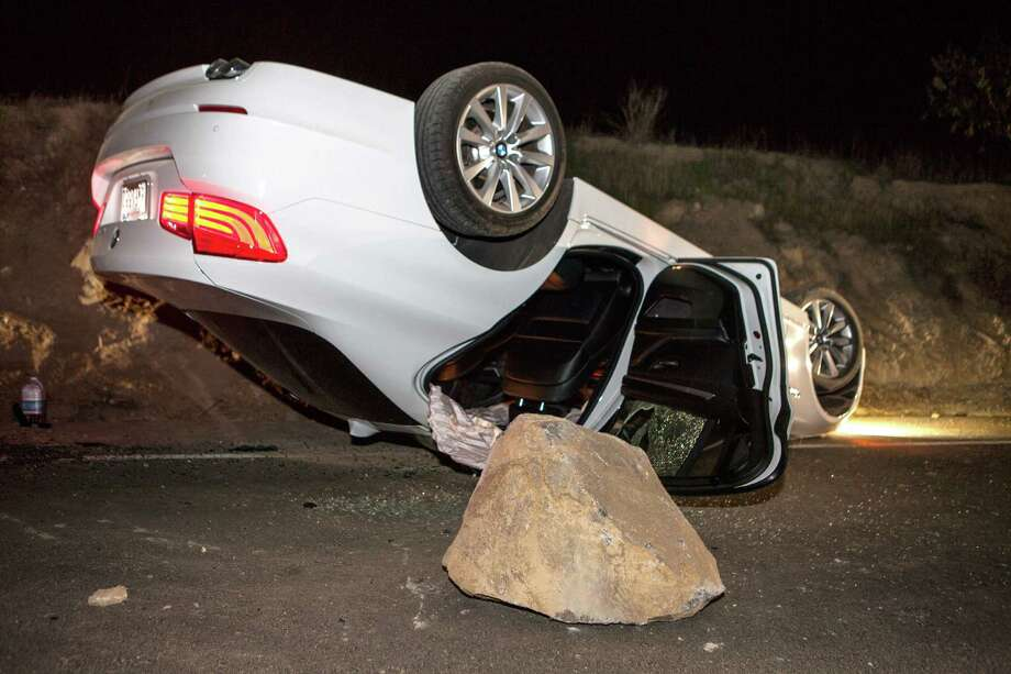 A car sits overturned on a highway in the Carbon Canyon area of Brea, Calif., Friday night, March 28, 2014, after hitting a rock slide caused by an earthquake. The people inside the car sustained minor injuries. A magnitude-5.1 earthquake centered in the area near Los Angeles caused no major damage but jittered nerves throughout the region as dozens of aftershocks struck into the night. Photo: Kevin Warn, AP / AP2014
