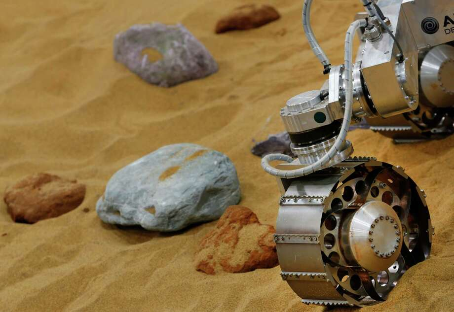 "A robotic vehicle on the 'Mars Yard Test Area', a testing ground for the robotic vehicles of the European Space Agency's ExoMars program scheduled for 2018, moves in Stevenage, England, Thursday, March 27, 2014. It looks like a giant sandbox - except the sand has a reddish tint and the ""toys"" on display are very expensive prototypes designed to withstand the rigors of landing on Mars. The scientists here work on the development of the autonomous navigation capabilities of the vehicle, so by being in communication with controllers on earth twice a day, will be able to use the transmitted information to navigate to new destinations on Mars. But it won't be fast - maximum range is about 70 meters (210 feet) per day. Photo: Lefteris Pitarakis, AP / AP2014"