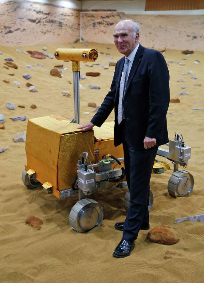 "Britain's Business Secretary Vince Cable poses for the photographers next to a robotic vehicle being tested on the 'Mars Yard Test Area', the testing ground of the European Space Agency's ExoMars program scheduled for 2018, in Stevenage, England, Thursday, March 27, 2014. It looks like a giant sandbox - except the sand has a reddish tint and the ""toys"" on display are very expensive prototypes designed to withstand the rigors of landing on Mars. The scientists here work on the development of the autonomous navigation capabilities of the vehicle, so by being in communication with controllers on earth twice a day, will be able to use the transmitted information to navigate to new destinations on Mars. Photo: Lefteris Pitarakis, AP / AP2014"