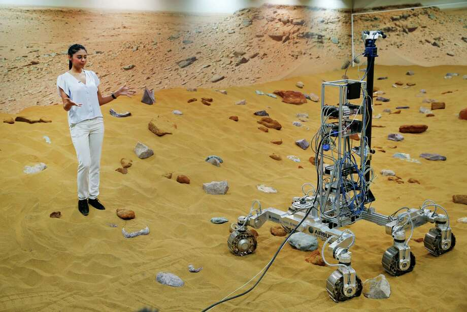 "A TV journalist reports on the 'Mars Yard Test Area', the testing ground for the robotic vehicles of the European Space Agency's ExoMars program scheduled for 2018, in Stevenage, England, Thursday, March 27, 2014. It looks like a giant sandbox - except the sand has a reddish tint and the ""toys"" on display are very expensive prototypes designed to withstand the rigors of landing on Mars. The scientists here work on the development of the autonomous navigation capabilities of the vehicle, so by being in communication with controllers on earth twice a day, will be able to use the transmitted information to navigate to new destinations on Mars. Photo: Lefteris Pitarakis, AP / AP"