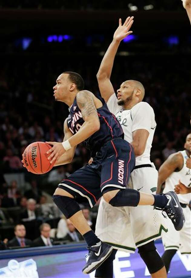 Connecticut's Shabazz Napier,  left, goes up to shoot past Michigan State's Adreian Payne in the first  half of a regional final at the NCAA college basketball tournament on  Sunday, March 30, 2014, in New York. (AP Photo/Seth Wenig)