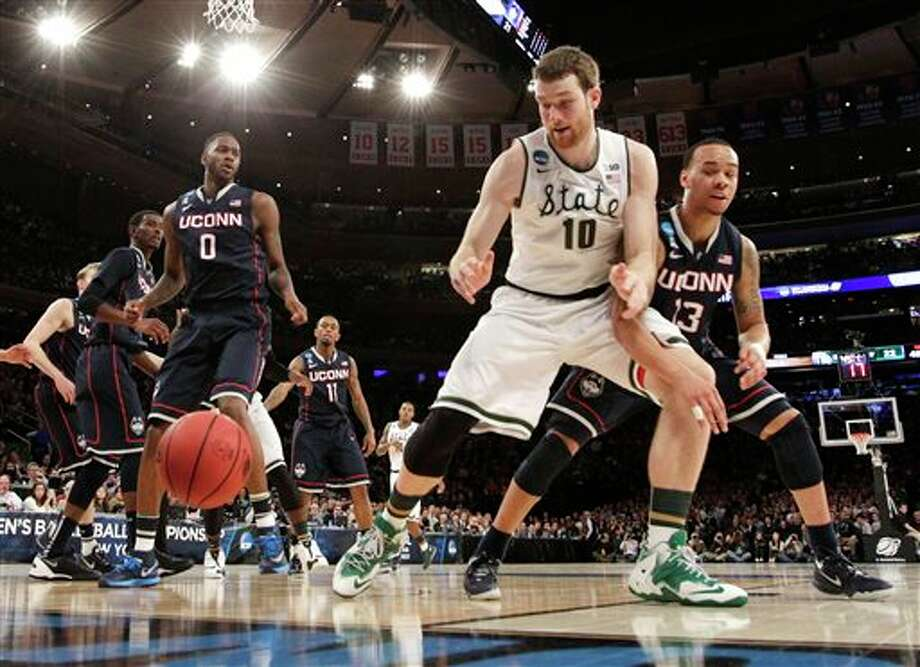 Michigan State's Matt  Costello, center, looks for the ball while covered by Connecticut's  Shabazz Napier, right, in the first half of a regional final at the NCAA  college basketball tournament on Sunday, March 30, 2014, in New York.  Connecticut's Phillip Nolan, left, looks on. (AP Photo/Frank Franklin  II)