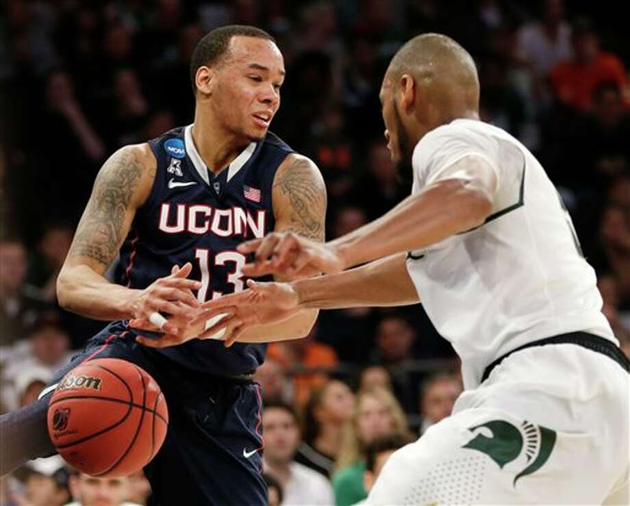 Connecticut's Shabazz Napier  loses the ball while covered by Michigan State's Adreian Payne in the  first half of a regional final at the NCAA college basketball tournament  on Sunday, March 30, 2014, in New York. (AP Photo/Seth Wenig)