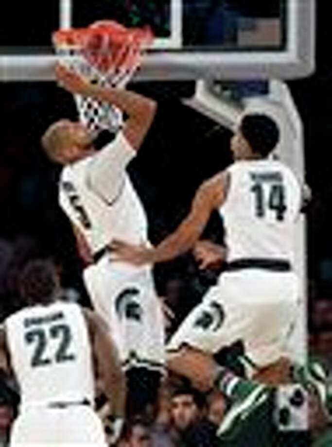 Michigan State's Adreian  Payne, left, and Gary Harris jump under the basket in the second half of  a regional final at the NCAA college basketball tournament against  Connecticut, Sunday, March 30, 2014, in New York. Michigan State's  Branden Dawson is at bottom. (AP Photo/Seth Wenig)