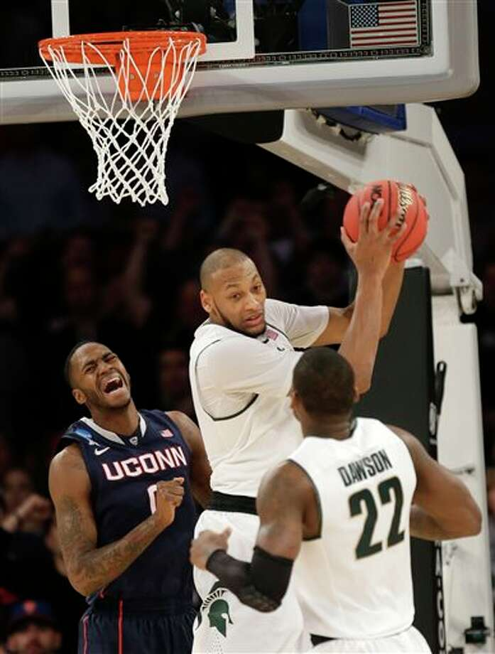 Michigan  State's Adreian Payne, center, grabs a rebound near Connecticut's  Phillip Nolan, left, and Michigan State's Branden Dawson in the second  half of a regional final at the NCAA college basketball tournament on  Sunday, March 30, 2014, in New York. (AP Photo/Seth Wenig)