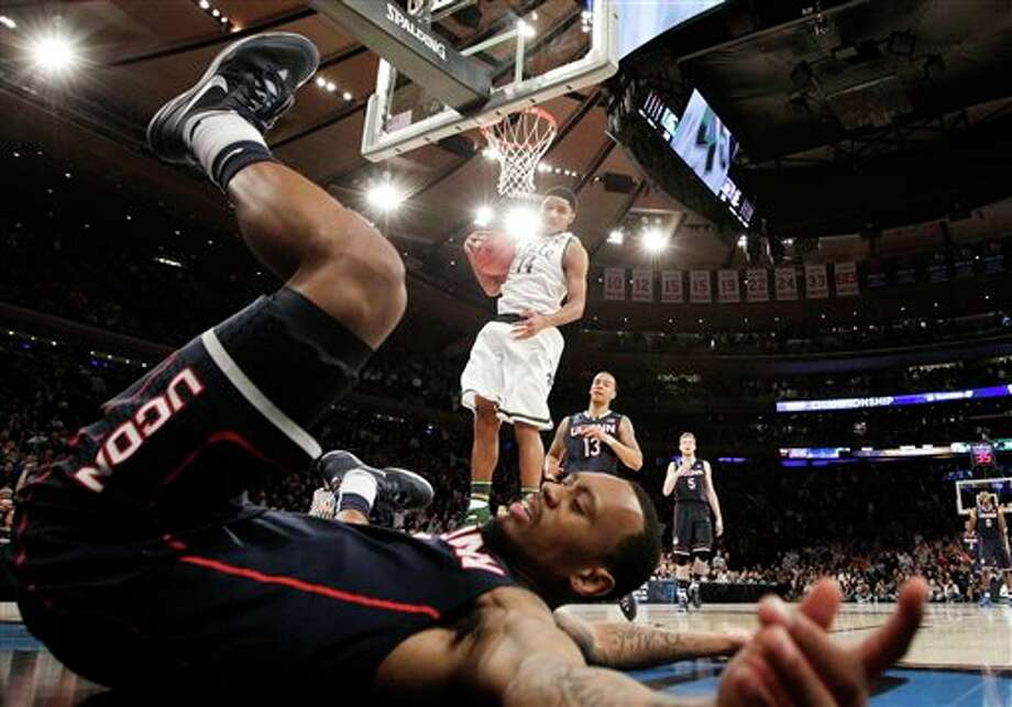 Connecticut's Ryan Boatright  lands on the floor after scoring as Michigan State's Gary Harris holds  the ball in the second half of a regional final at the NCAA college  basketball tournament on Sunday, March 30, 2014, in New York. (AP  Photo/Frank Franklin II)