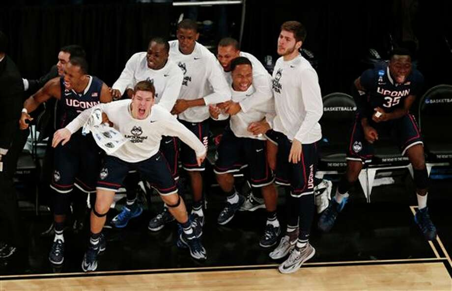 Connecticut players react  during the second half in a regional semifinal at the NCAA college  basketball tournament against the Michigan State, Sunday, March 30,  2014, in New York. (AP Photo/Julio Cortez)