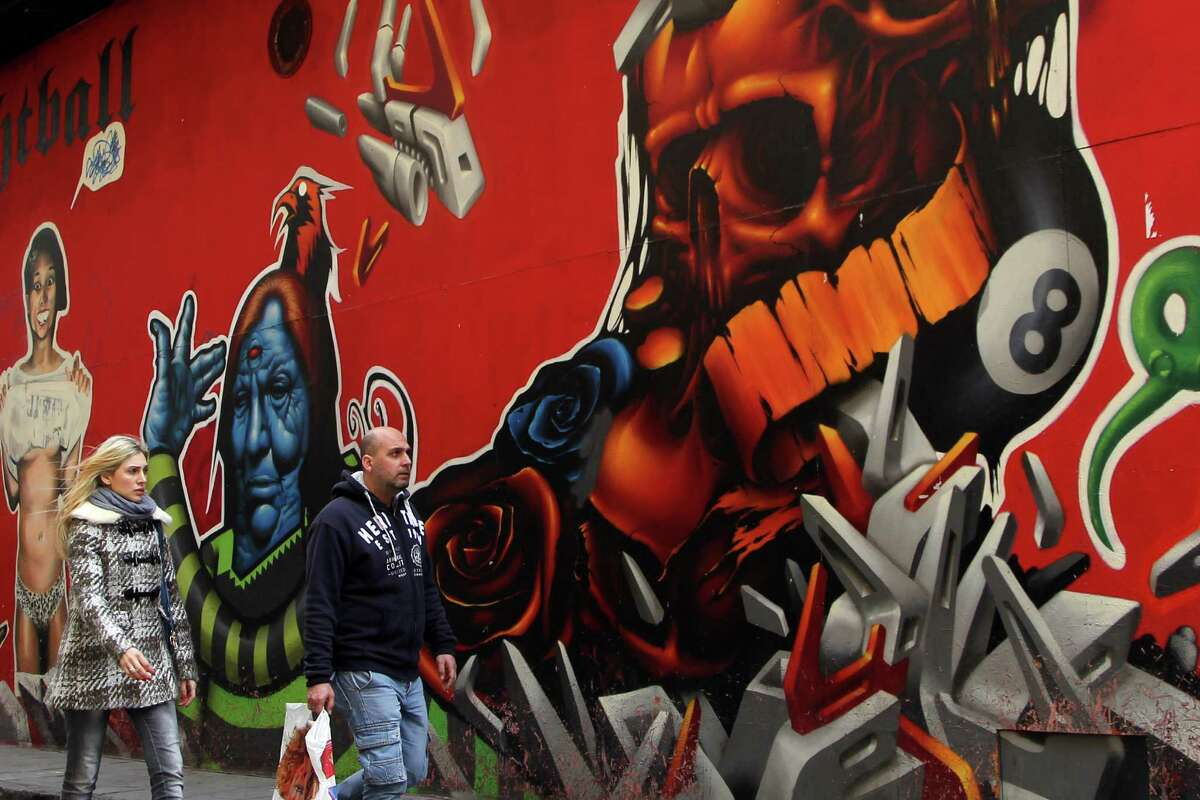 People pass by a graffiti a decoration for a closed night club in the