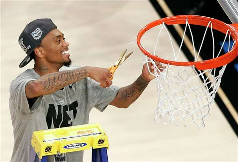 Connecticut guard Ryan  Boatright cuts a strand of the netting on the rim after his team  defeated Michigan State 60-54 during a regional final at the NCAA  college basketball tournament, Sunday, March 30, 2014, in New York. (AP  Photo/Julio Cortez)
