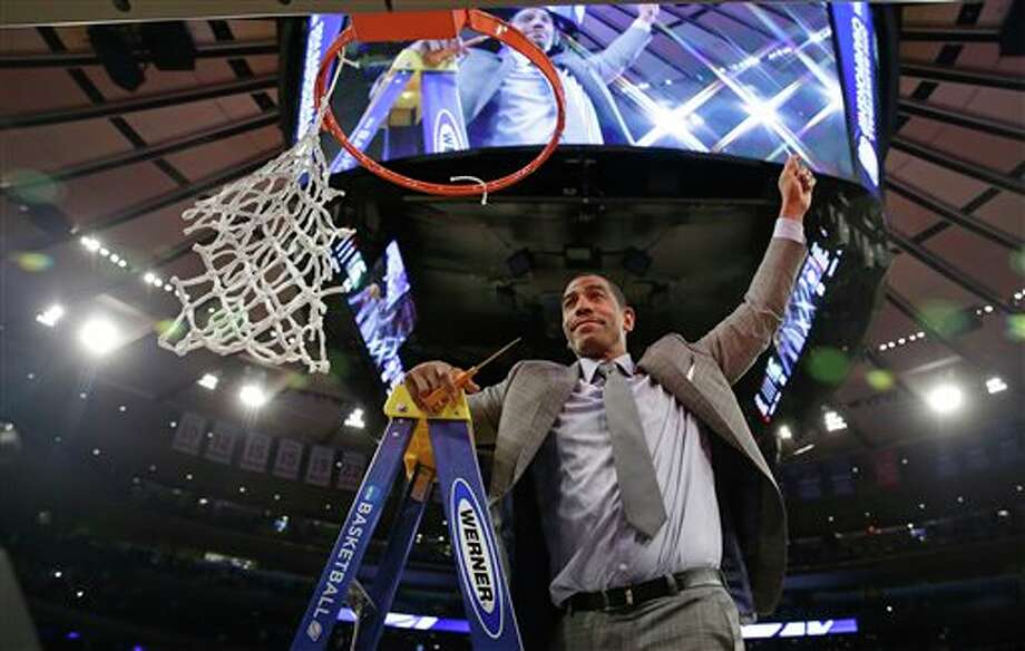 Connecticut head coach Kevin  Ollie gestures to the crowd before cutting down the net after a regional  final against Michigan State in the NCAA college basketball tournament   Sunday, March 30, 2014, in New York. Connecticut won the game 60-54.  (AP Photo/Seth Wenig)