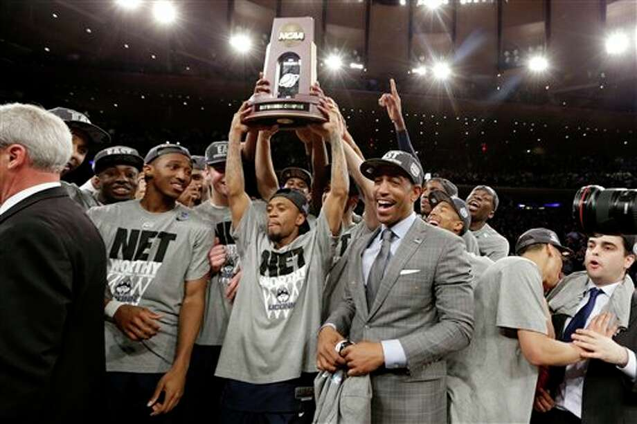 Connecticut head coach Kevin  Ollie, center right, celebrates with his team after beating Michigan  State 60-54 during a regional final at the NCAA college basketball  tournament, Sunday, March 30, 2014, in New York. (AP Photo/Frank  Franklin II)