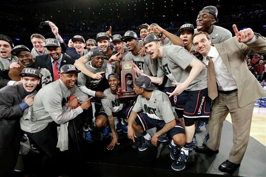 The Connecticut team poses  for photographs after a regional final against Michigan State in the  NCAA college basketball tournament ,Sunday, March 30, 2014, in New York.  Connecticut won 60-54. (AP Photo/Frank Franklin