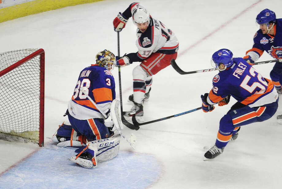 Hartford's Darroll Powe directs a shot on Sound Tiger goalie Kevin Poulin in the first period of their AHL hockey game at the Webster Bank Arena in Bridgeport, Conn. on Sunday, March 30, 2014. Also defending on the play are Sound Tigers Joe Finley and Riley Wetmore. Photo: Brian A. Pounds / Connecticut Post
