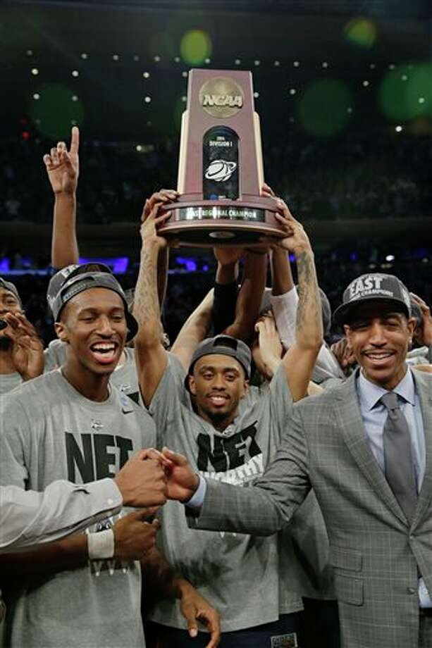 Connecticut head coach Kevin  Ollie, right, celebrates with his team as Ryan Boatright, center, holds  the championship trophy, after the NCAA college basketball tournament  Sunday, March 30, 2014, in New York. Connecticut won the game 60-54. (AP  Photo/Seth Wenig)