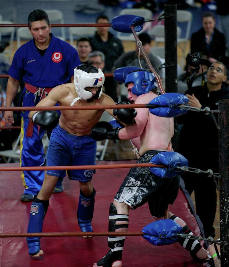 "Santos Escribano, of Danbury, left, and David Padua, of Elizabeth, New Jersey, during the Professional Kickboxing Federation Super Welter-Weight title bout held at the ""Battle of the Tri-State Warriors"" a kickboxing, boxing and wrestling event held at the Bill S. Curtis Harambee Center in Danbury, Conn, on Saturday night, March 29, 2014. Escrabano won the match. Ring Referee Jonas Nunez Jr. looks on. Photo: H John Voorhees III / The News-Times Freelance"