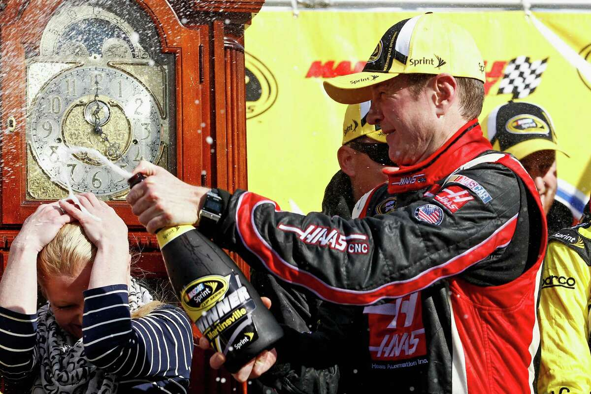 MARTINSVILLE, VA - MARCH 30: Kurt Busch, driver of the #41 Haas Automation Chevrolet, celebrates in Victory Lane with his girlfriend Patricia Driscoll after winning during the NASCAR Sprint Cup Series STP 500 at Martinsville Speedway on March 30, 2014 in Martinsville, Virginia. (Photo by Jeff Zelevansky/Getty Images) ORG XMIT: 463750147