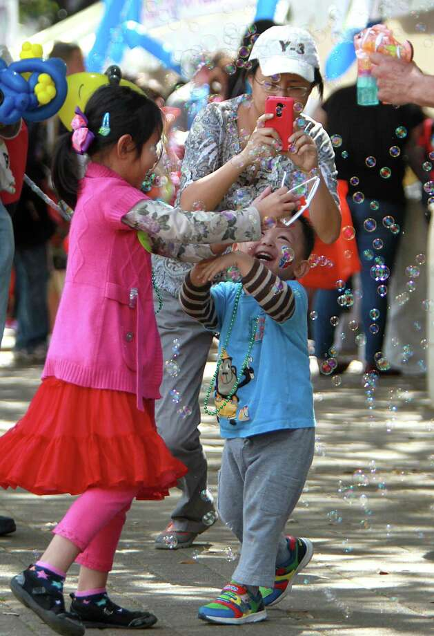 Cynthia Chen, 6, and Ryan Chen, 2, chase bubbles during the McDonald's Houston Children's Festival at City Hall on March 27, 2014, in Houston, Tx. The festival will benefit the  Child Advocates Inc. and presented by Baker Hughes. Photo: Mayra Beltran, Houston Chronicle / © 2014 Houston Chronicle