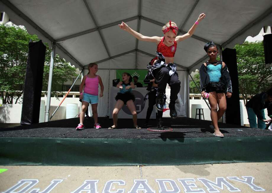 Emerson Stielow, 9, of Stacey's Dance Studio, jumps off the stage as kids start to line up for a mini Zumba kids class during the McDonald's Houston Children's Festival at City Hall on March 27, 2014, in Houston, Tx. The festival will benefit the  Child Advocates Inc. and presented by Baker Hughes. Photo: Mayra Beltran, Houston Chronicle / © 2014 Houston Chronicle
