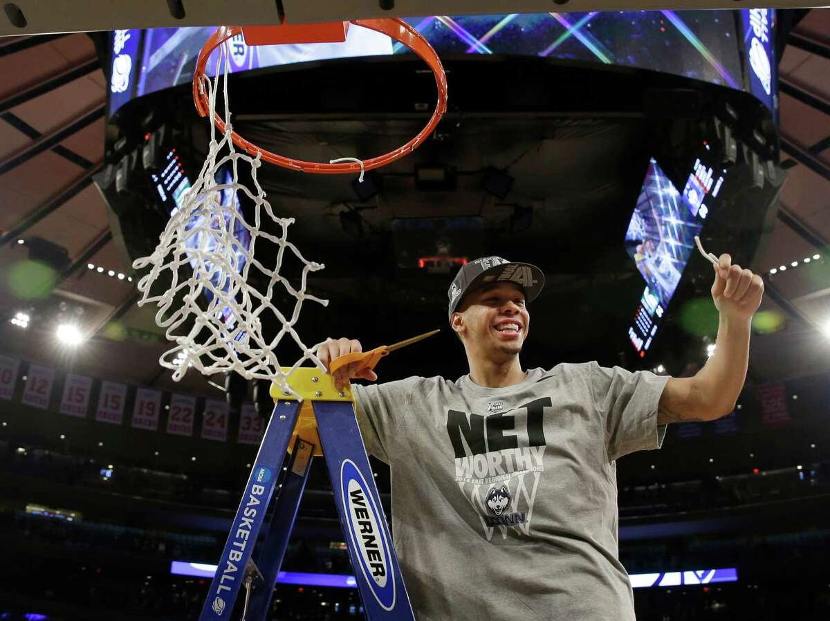Connecticut's Shabazz Napier smiles after cutting the net after a regional final against Michigan State in the NCAA college basketball tournament Sunday, March 30, 2014, in New York. Connecticut won the game 60-54. (AP Photo/Seth Wenig) ORG XMIT: NYFF102
