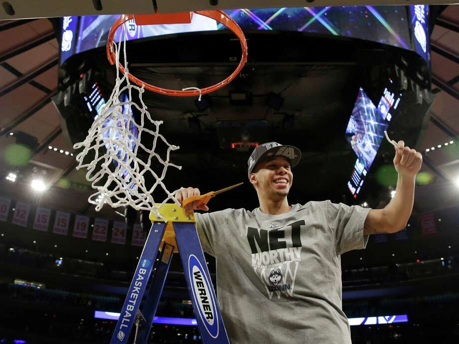 Connecticut's Shabazz Napier smiles after cutting the net after a regional final against Michigan State in the NCAA college basketball tournament Sunday, March 30, 2014, in New York. Connecticut won the game 60-54. (AP Photo/Seth Wenig) ORG XMIT: NYFF102 Photo: Seth Wenig / AP