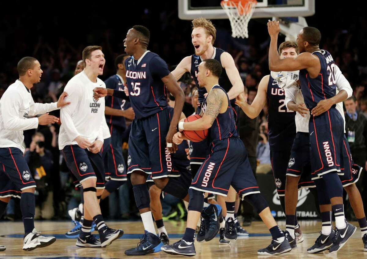 Connecticut players celebrate after beating Michigan State 60-54 in a regional final at the NCAA college basketball tournament, Sunday, March 30, 2014, in New York. (AP Photo/Seth Wenig) ORG XMIT: MSG127