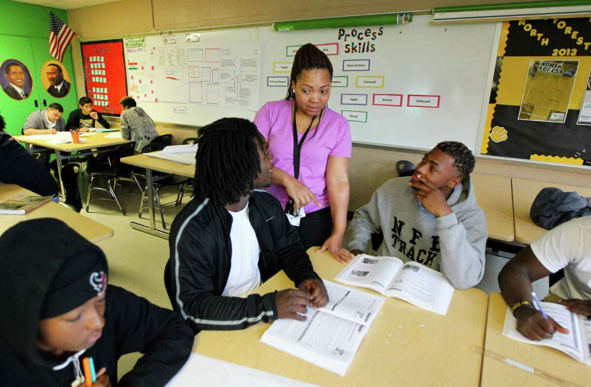 Sonya Gilford Fontenot talks with Dayvante Brimzy, left, and James Randle in her U.S. History class. North Forest High school has been under Houston ISD supervision for one year after North Forest ISD was dissolved by the state.