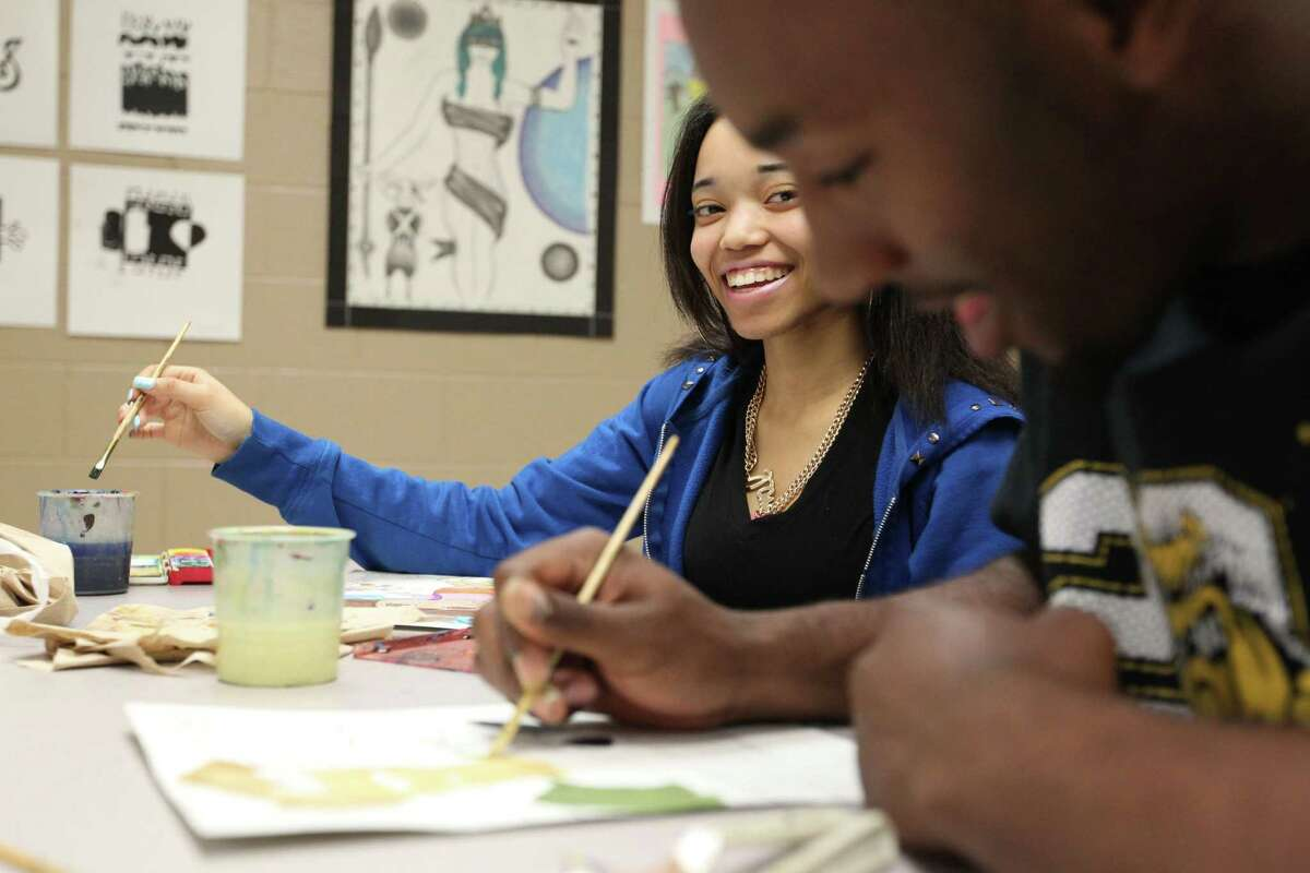 North Forest High School students Amanda Wallace and Jarvis Harris paint during art class.