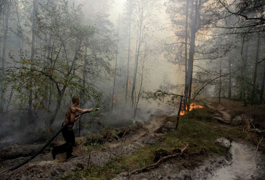 FILE - In this Aug. 7, 2010 file photo,  a firefighter tries to stop a forest fire near the village of Verkhnyaya Vereya in Nizhny Novgorod region, some 410 km (255 miles) east of Moscow. Twenty-first century disasters such as killer heat waves in Europe, wildfires in the United States, droughts in Australia and deadly flooding in Mozambique, Thailand and Pakistan highlight how vulnerable humanity is to extreme weather, says a massive new report from a Nobel Prize-winning group of scientists released early Monday, March 31, 2014. (AP Photo/Alexander Zemlianichenko Jr., File) Photo: Alexander Zemlianichenko Jr, STR / AP