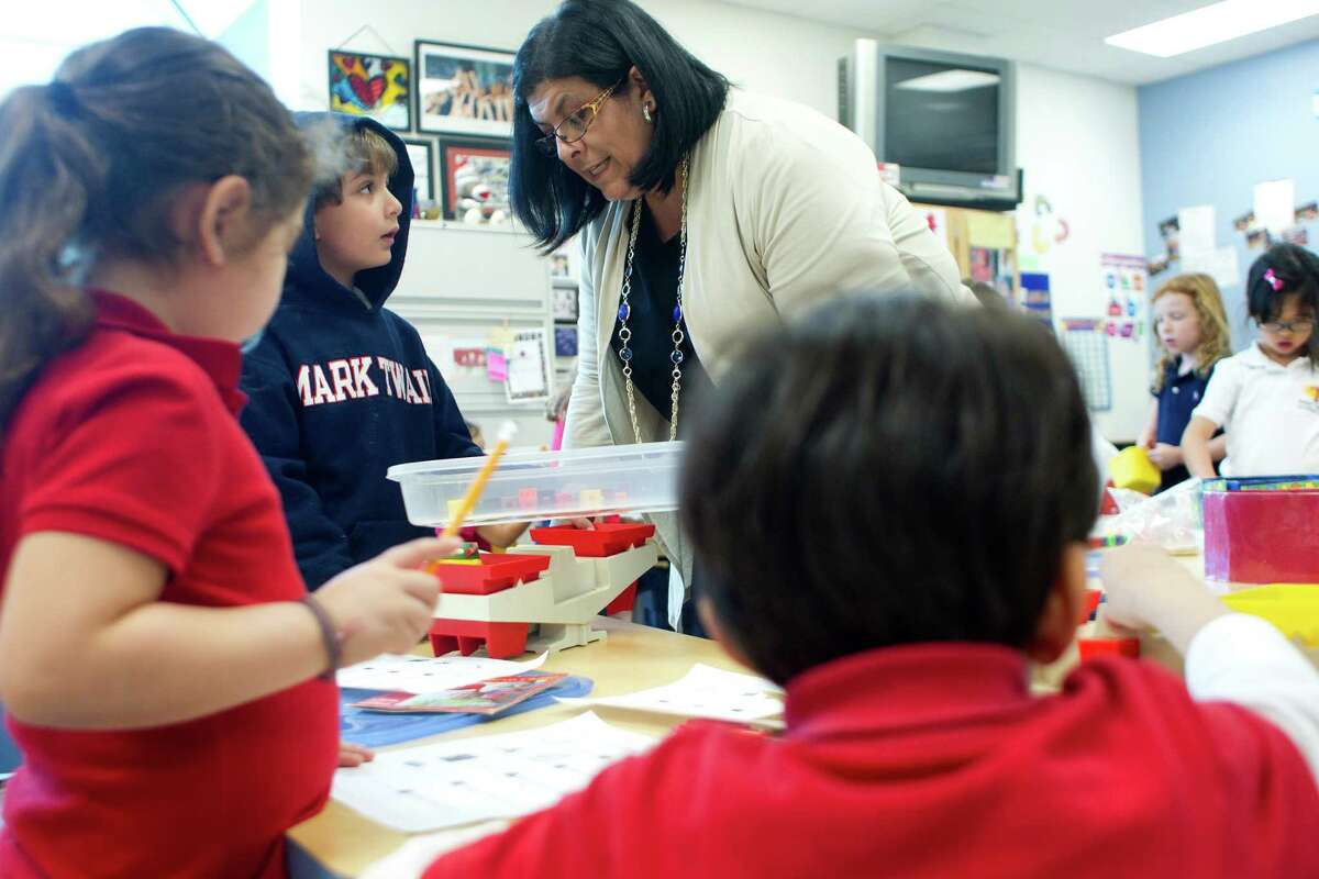 Speaking in Spanish, teacher Graciela Martinez works with kindergartner Alejandro Gerlein, 6, on a lesson about weight measurement in the dual-language program at Mark Twain Elementary.
