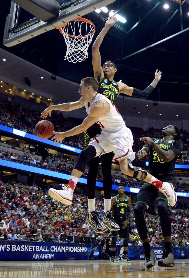 Wisconsin guard Josh Gasser passes around Baylor center Isaiah Austin. Photo: Mark J. Terrill, Associated Press