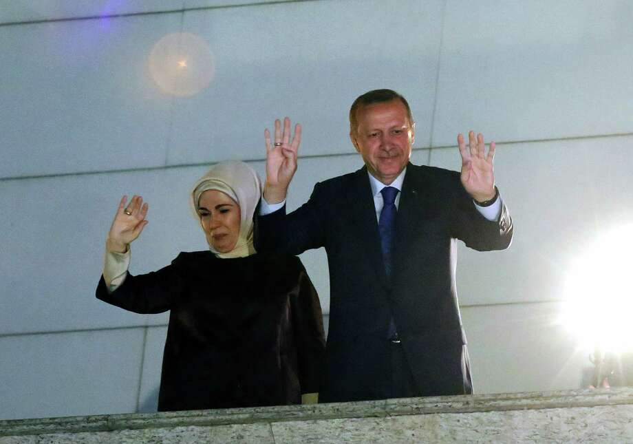 Turkey's Prime Minister Recep Tayyip Erdogan and his wife Emine Erdogan wave to supporters from the balcony of his ruling party headquarters in Ankara, Turkey, early Monday, March 31, 2014. Erdogan on Sunday hailed what appeared to be a clear victory in local elections, providing a boost that could help him emerge from a spate of recent troubles. Erdogan was not on the ballots in the countrywide polls, but with about half of votes counted, Turkish newswires suggested that his party was significantly outstripping its results in the last local elections of 2009 and roundly beating the main opposition party. Photo: AP / AP