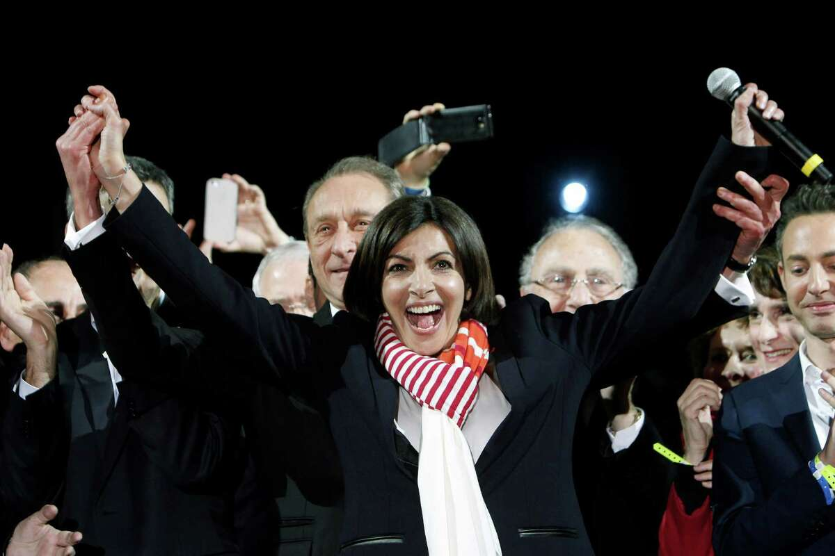 French Socialist Party deputy mayor of Paris, Anne Hidalgo, center, smiles, as outgoing mayor Bertrand Delanoe, stands behind her, during a speech after results were announced in the second round of the French municipal elections, in Paris, Sunday, March 30, 2014. Hidalgo saved Paris for the flagging Socialist Party in Sunday's municipal elections, becoming the French capital's first female mayor.