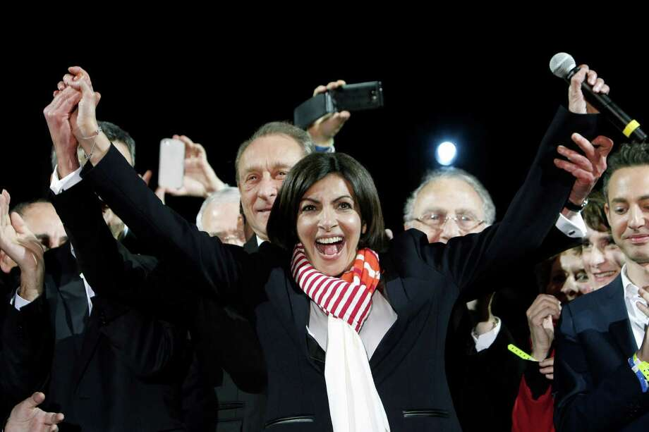 French Socialist Party deputy mayor of Paris, Anne Hidalgo, center, smiles, as outgoing mayor Bertrand Delanoe, stands behind her, during a speech after results were announced in the second round of the French municipal elections, in Paris, Sunday, March 30, 2014. Hidalgo saved Paris for the flagging Socialist Party in Sunday's municipal elections, becoming the French capital's first female mayor. Photo: Thibault Camus, AP / AP