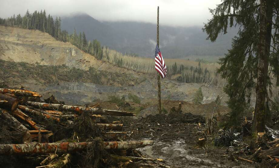A flag flies at half-staff on a log with the slope of the massive mudslide that struck Oso in the background near Darrington, Washington March 30, 2014. The official death toll from the March 22 catastrophe northeast of Seattle stood at 18, based on the number of victims whose bodies have been recovered and positively identified by medical examiners. But Snohomish County authorities have acknowledged finding 10 more sets of remains that have yet to be identified, putting the overall presumed body count at 28.  REUTERS/Ted S. Warren/Pool  (UNITED STATES - Tags: DISASTER ENVIRONMENT TPX IMAGES OF THE DAY) Photo: Pool, Reuters