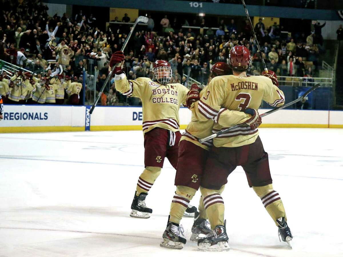 Boston College's Ian McCoshen celebrates with teammates after his goal against UMass Lowell in the third period of the NCAA Northeast Regional hockey final in Worcester, Mass., Sunday, March 30, 2014. Boston College won 4-3.(AP Photo/Elise Amendola) ORG XMIT: MAEA110